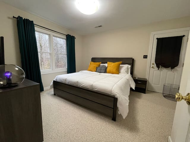 King bedroom featuring fresh plush bedding and amazing view of the woods.