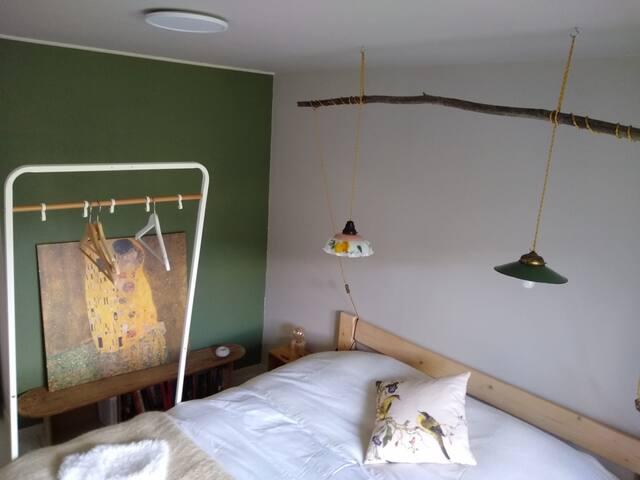 Lit bio 180/200, un futon rempli de fibres biologique (laine, coton, coco, ...) repose sur des matelas en latex naturel.  Chambre à côté de la salle de bain et vu sur le jardin et le paysage. Levé du soleil au matin.