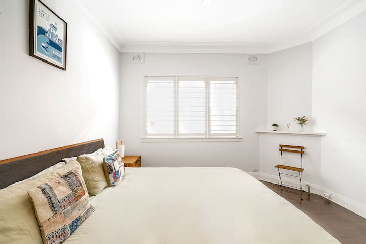 A spacious bedroom features natural light, a comfortable king bed and built-in wardrobes for convenience