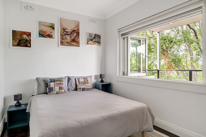 A second bedroom has a queen bed and streams of light coming in through the large, foldable window that looks out to the balcony