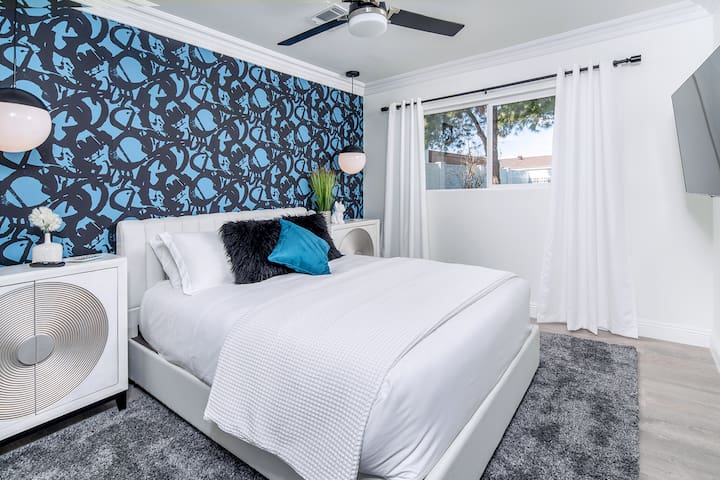 The master bedroom has a queen sized bed, vanities with lots of storage, a huge Smart TV, a ceiling fan, walk in closet, and full bathroom.