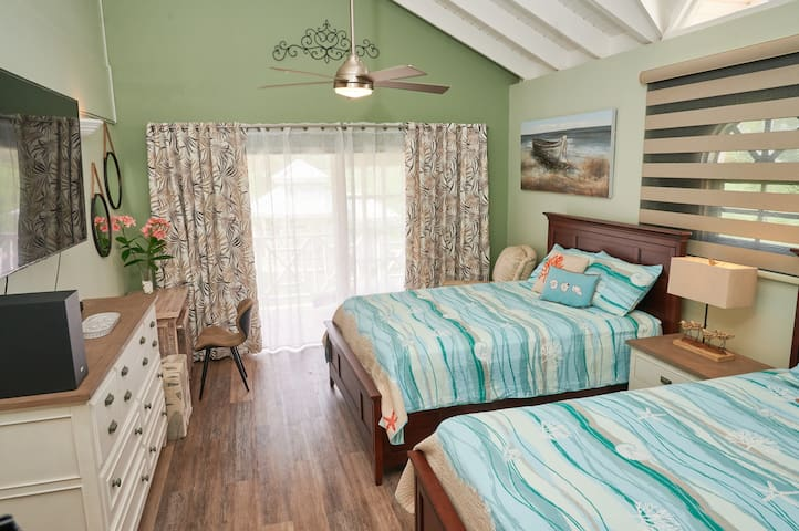 """Bedroom outfitted with two queen size beds, air conditioning, 65"""" flat screen television, sound system, ceiling fan, laminated flooring..."""