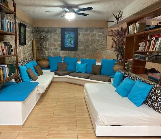 Sala que incluye una cama individual y una colchoneta que se usa también como cojín largo para sentarse en la sala.