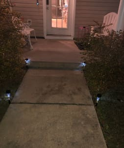 A path way which leads you front porch of the house and has a step right before the front porch