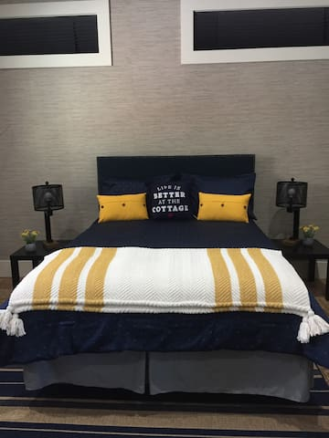 Queen bed, in a large bedroom with sitting area, work office desk, and a Smart TV.