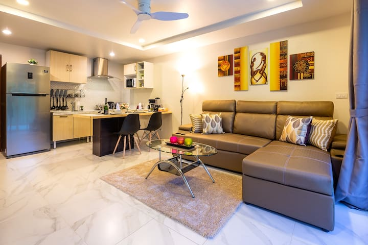 The large living room has a modern open kitchen, a pull-out sofa bed (queen size), and is equipped with Smart TV.