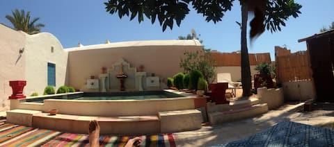 Petite maison typique dans un parc  avec piscine.