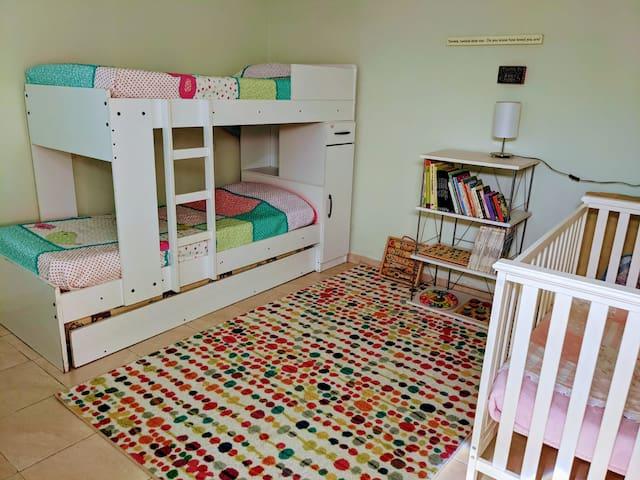 Habitación con litera de 3 camas, cuna y  practicuna.