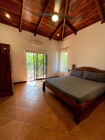 The spacious bedroom features a king sized bed, AC, ceiling fan, flat screen tv with cable, a wardrobe and a view the open field behind.