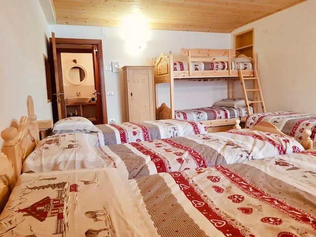 Camerata con un letto a castello e letti singoli, bagno con aspiratore.