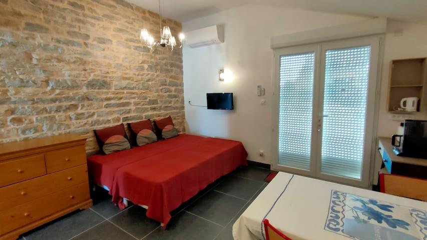 Salon, cuisine ouverte avec deux lits simple.