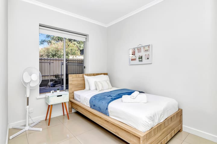A secondary bedroom sleeps one person in a single bed and features a bedside table, a fan and a large window