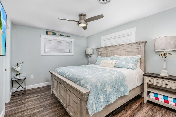 The master bedroom has a king size bed, a closet for clothes storage and a wall mounted smart TV.