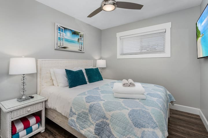 Queen size bed with closet and wall mounted TV.