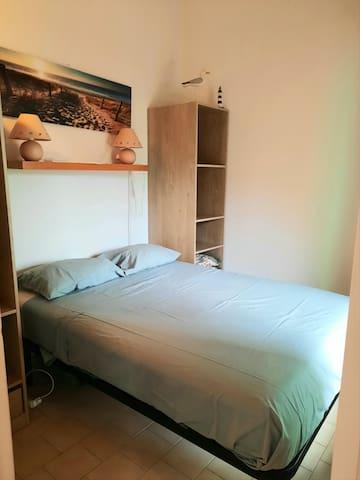 Chambre lit double avec dressings ouverts et porte fenêtre donnant sur la terrasse