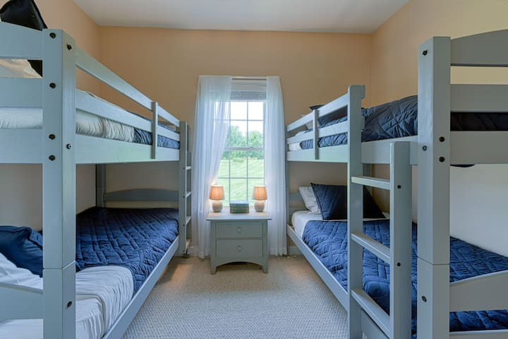 Bunk room has two bunk bed, four twin-sized beds, a double closet (with drawer storage inside), and two bean bag chairs.