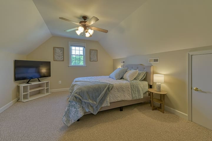 upstairs bedroom features queen-sized bed, television, en suite bathroom, with space for roll-away cot and/or pack and play