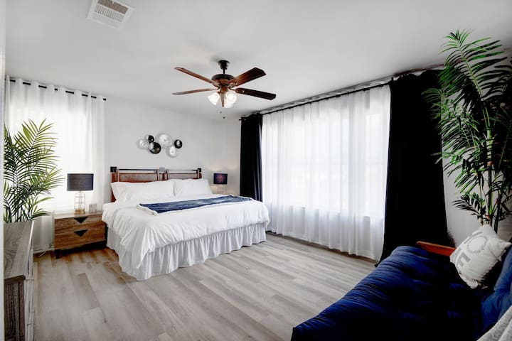 Master Bedroom with a ceiling fan, extra window a/c unit, blackout curtains, and a sofa-bed.