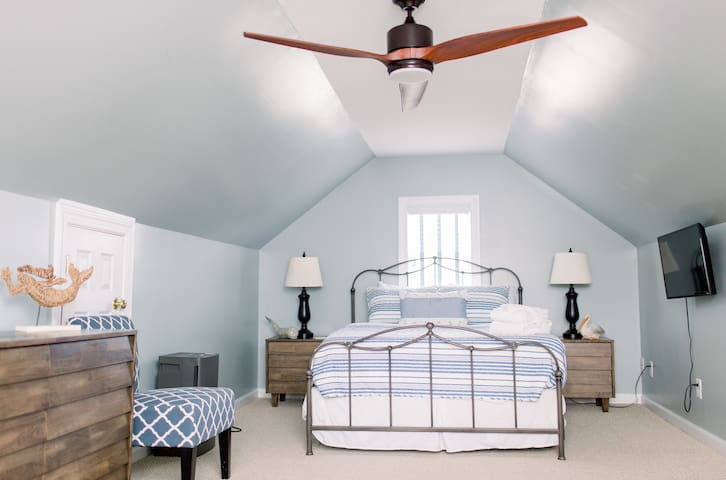 Bedroom Four, on the third floor, offers a quiet retreat with a queen-size bed, TV, and workspace.