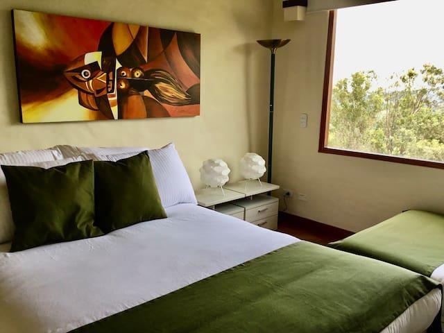 En nuestra habitación Hamsa podrás descansar de verdad. Es una amplia habitación con 2 tipos de acomodaciones (1 o 2 camas), colchón de primera y cómodo baño, además podrás admirar el amanecer y sus hermosas vistas al valle de Villa de Leyva.