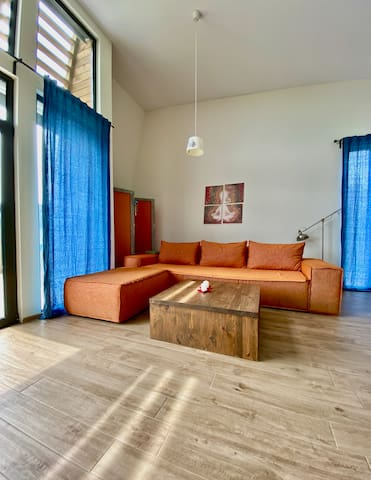 The sofa in the living area can accommodate several people. The table in front of it is made from real wood.
