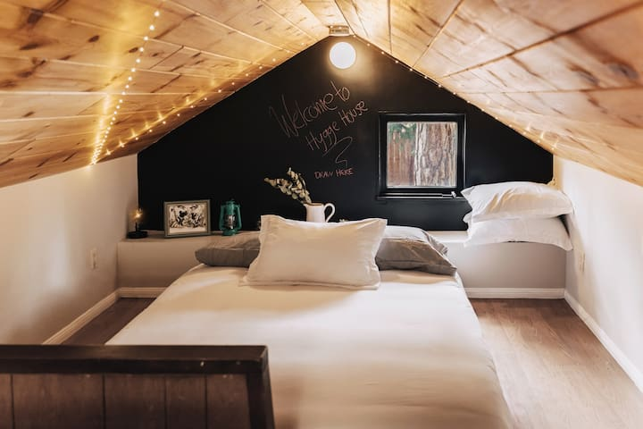 upstairs loft with one QUEEN & one TWIN bed, television, twinkle lights, chalkboard wall & games! #treehousevibes