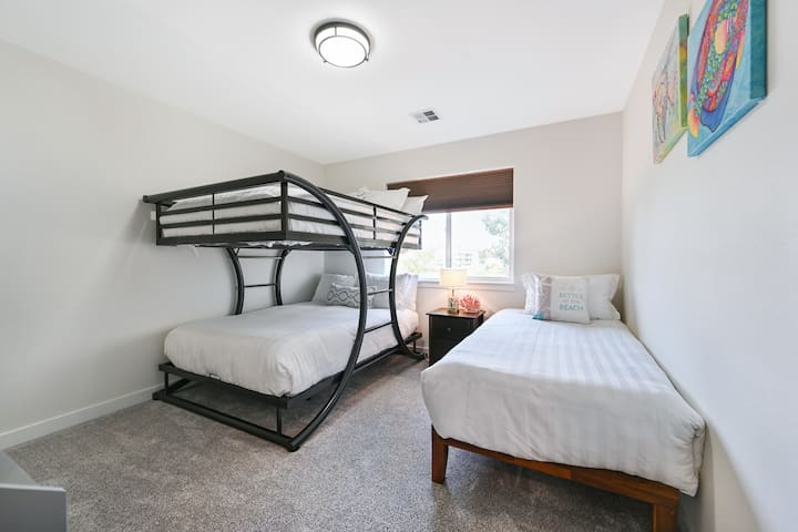 Guest room with full size bunk beds and a twin bed