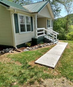 Concrete walkway from drive to front porch steps.  Floodlight on porch to illuminate it at dark.