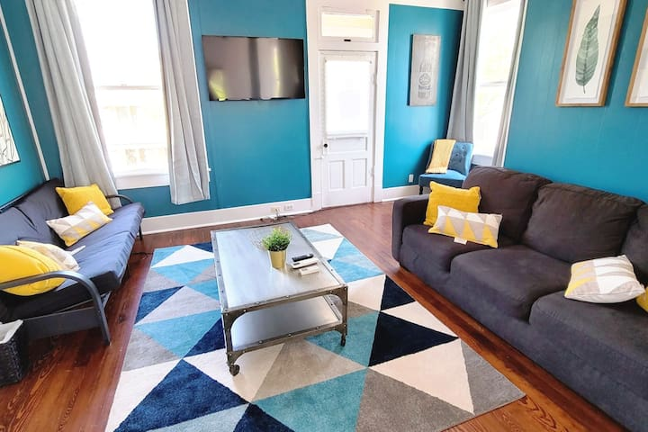 Stunning and bright living room with a couch and a futon. For your entertainment We have added a 50inch 4k tv with Netflix, hulu and hbo max.