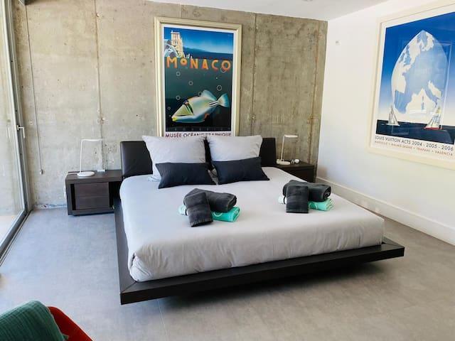 Master Schlafzimmer - ebenerdig - mit großer Glasfront und Blick auf den Garten mit Pool