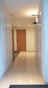 Entrée dans l'immeuble et porte d'entrée large de l'appartement.
