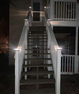 Solar post cap lighting providing lighting up outside stairway to entry.