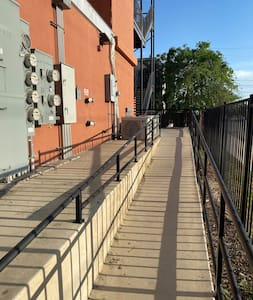 Ramp to apartment building with rails and lighting