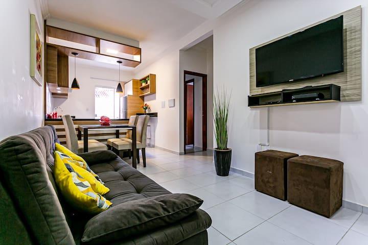 Sala de estar em conceito aberto com mesa de jantar, sofá-cama, TV com canais a cabo.