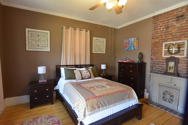Bedroom with an old fashion look and a fire place.