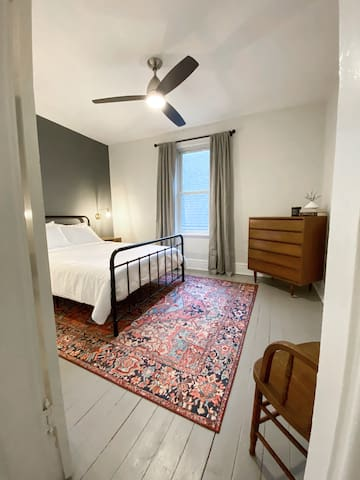 Upstairs second bedroom with a ceiling fan, queen Canadian made mattress, tall dresser, and closet