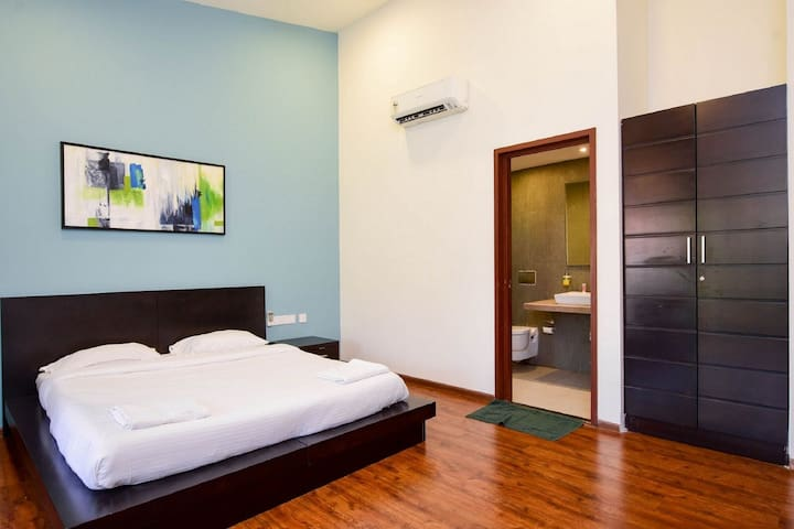 1st Bedroom - Air Conditioner, King size bed, bed side drawers, wardrobe, attached bathroom and a spacious garden styled attached balcony