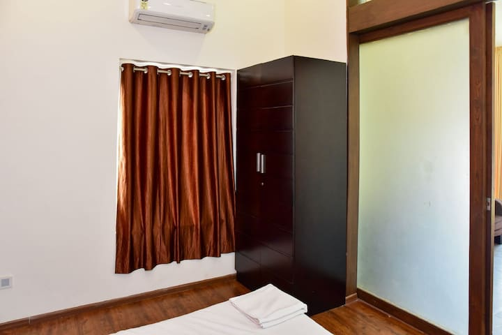 Bedroom - Air Conditioner, King size bed, bed side drawers, wardrobe, attached bathroom and a spacious garden styled attached balcony