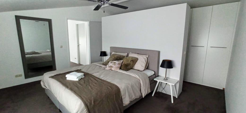 De grootste slaapkamer, voorzien van een heerlijke boxspring van 180 x 200, met een ruime kastenwand en privé wastafel.