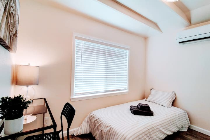 Relax in a beautifully Zen-designed room with Air Conditioning, desk, chair, night stand, wired ethernet, and Wifi.