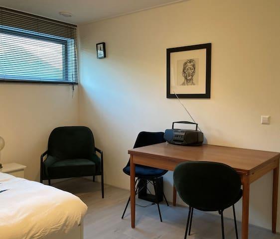 slaapkamer beneden met tweepersoons bed en plek om te werken