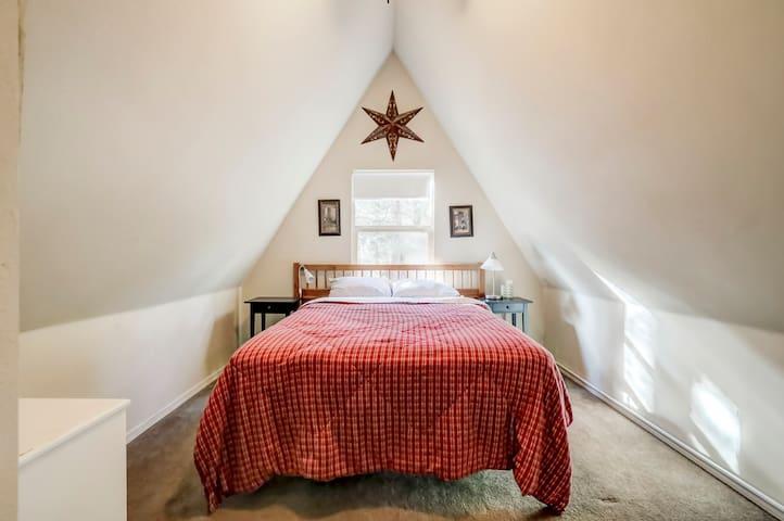 upstairs bedroom with queen bed, closets,  and door