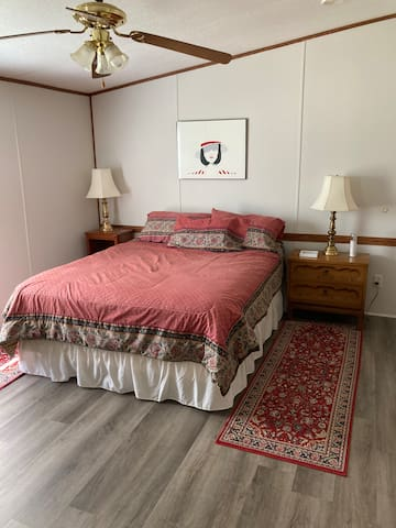 Master bedroom with queen bed and ceiling fan.  Bath connected.