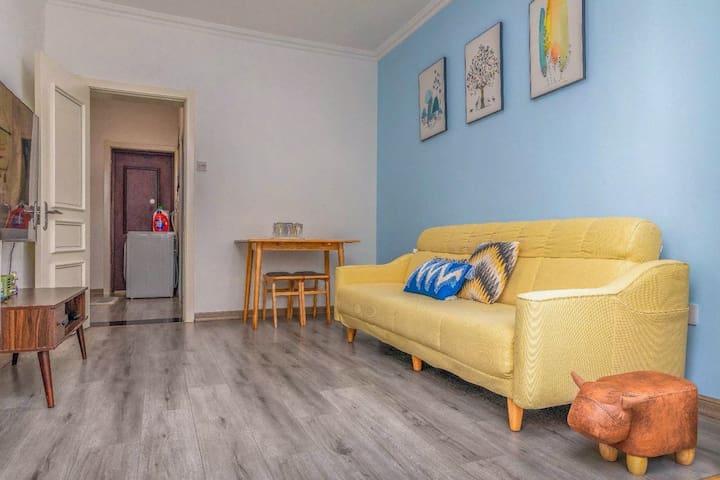 客厅宽敞明亮,配备三人位沙发、餐桌、液晶电视、电视柜、空气净化器、空调、暖气片等设施,一应俱全。
