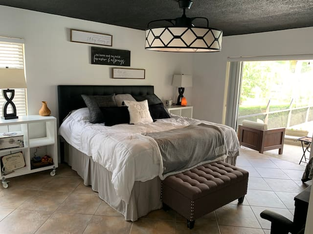 Master bedroom with King bed, ceiling fan, TV with firestick, and pocket sliding glass doors open to the pool area.