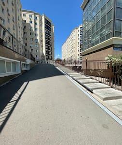 На входе в жилой комплекс имеется пандус для заезда автомобиля на территорию комплекса. Это один из способов добраться до квартиры. Второй способ - подъезд через паркинг, прямо к лифту.