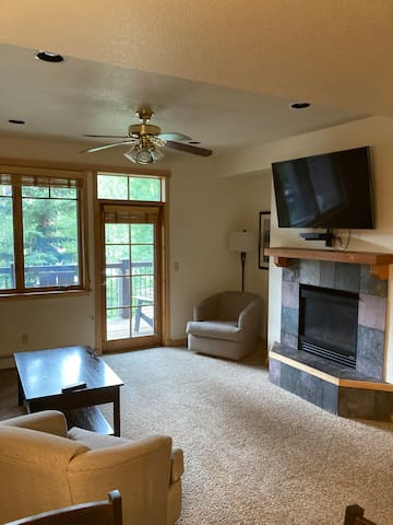 The living room has a gas fireplace, large tv and walk out porch, and a sofa couch.