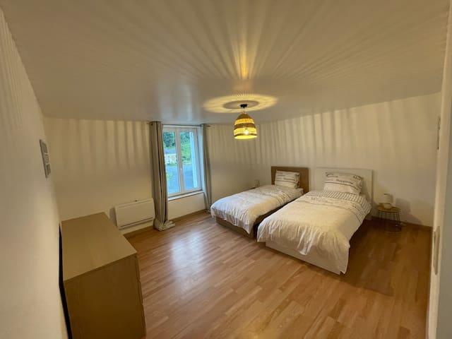 Chambre d'enfant avec deux lits simples de 90 x 200 cm et meuble de rangement avec 6 tiroirs.