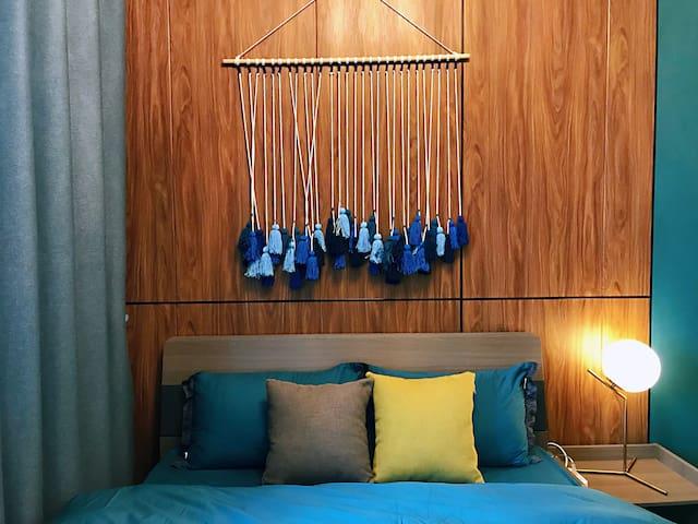 床头为定制实木背景墙、纺织品装饰物