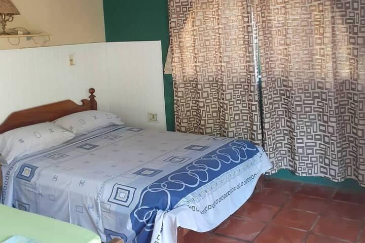 Habitación con una cama matrimonial y una cama individual